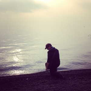 Justin kneeling by the Sea of Galilee on New Year's Day